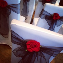 Black chair bow with red rose, chair cover hire, wedding decor and centrepieces from Lily Special Events, Glasgow and Scotland wedding hire